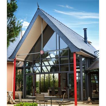 Extension massive d'une maison avec une toiture en ardoise