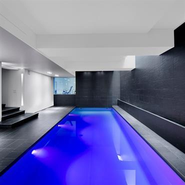 Piscine au sous-sol, carrelage noir et gris foncé, eau bleu électrique, mur et plafond blancs