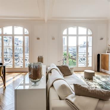 Un meuble bas laqué blanc délimite les zones salon - salle à manger, structurant l'espace sans cloisonner.