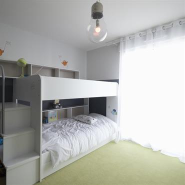 La chambre d'enfant , en code couleur gris et blanc se permet un écart ludique avec la moquette verte