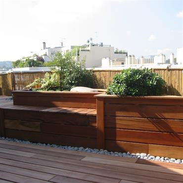 Terrasse en ville paysagée avec plancher de bois et structure multifonctions banc et jardinières en bois. Palissade en canisses pour s'abriter des regards.