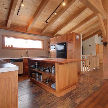 Cuisine de chalet de montagne, tout en bois et plan de travail blanc.