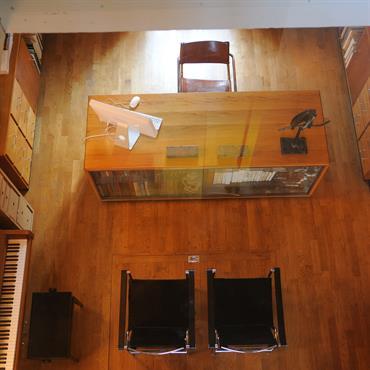 Vue de dessus du bureau au look entièrement en bois, par une ouverture vitrée dans le sol de l'étage