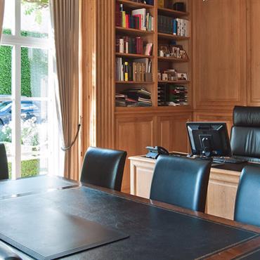 Bureau avec boiserie sur les murs. Fauteuils et chaises en cuir noir. Bibliothèque