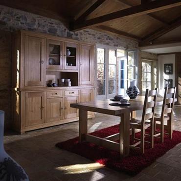 Salle à manger de style régionale. Pierres et poutres apparentes, meubles en chêne massif, pavés au sol.