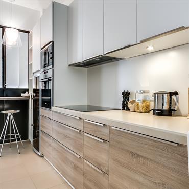 Les équipements et aménagements de la cuisine misent sur le bois, l'acier et la laque pour offrir une touche contemporaine à cet appartement ancien d'esprit haussmannien.