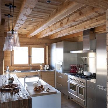 La cuisine contemporaine s'intègre à merveille dans l'environnement chalet à la charpente en bois et au plancher brut à larges lattes.