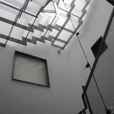 Comment apporter de la lumière et éclairer une cage d'escalier. Cage d'escalier moderne éclairée par un puits de lumière. Escalier design transparent avec limon central en acier.