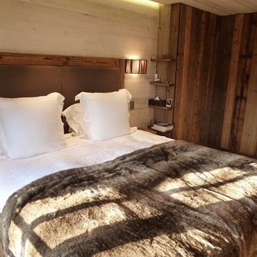 Chambre avec murs en lambris. Mur de tête de lit plus en bois plus clair