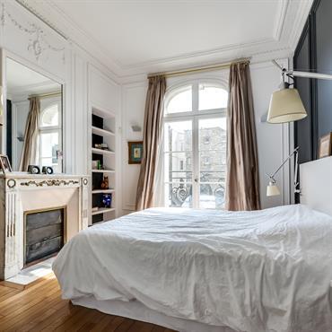 Mélange de styles dans la chambre parentale de cet appartement haussmannien où les éclairages tantôt design, tantôt baroque contribuent au décor de caractère.