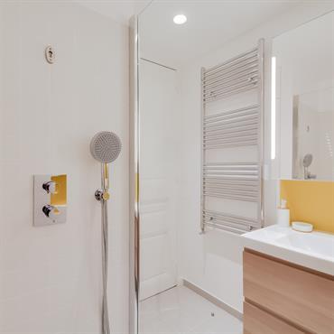 Le jaune que l'on retrouve par touches dans une salle de bain dominée par le blanc mat du carrelage apporte une ambiance lumineuse.