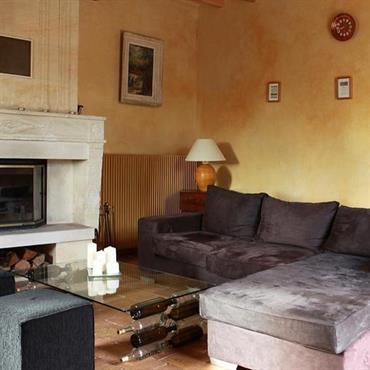 Le salon avec ses canapés et la cheminée du XVIII° siècle.