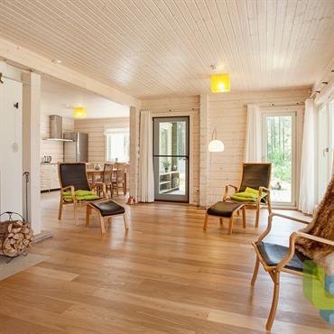 Salon d'ambiance scandinave avec cheminée. Parquet finition huilé, murs et plafond en lambris peint en blanc.