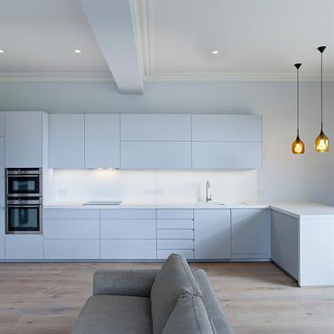 Le plan de travail de la cuisine est en trois parties avec plaque de cuisson integrée, évier sous-plan avec pente égouttoir intégrée. La crédence est habillée en Panbeton®. Le jambage ...