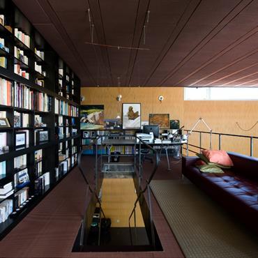 Le système Ya Ya Oh d'Ingo Maurer éclaire la trémie de l'escalier d'acier brut. Le bureau de la série Nomos, dessinée par Norman Foster pour Tecno, est complété par la ...