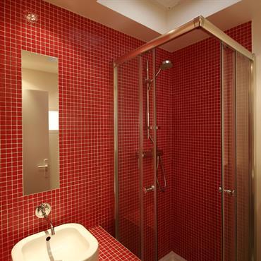 Salle d'eau en mosaïque rouge et puit de lumière