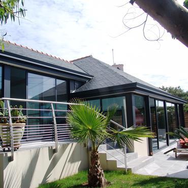Couverture d'une piscine avec un toit en ardoise et des baies vitrées