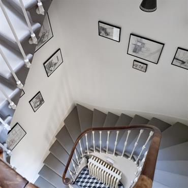 Cage d'escalier carrée aménagée de cadres photos. Escalier e bois peint en gris, rampe en bois