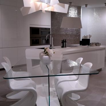 Salle à manger avec table en verre à coins arrondis. Chaises design blanches. Lustre design blanc. Vue sur la cuisine avec îlot central blanc. Murs dans les tons de gris ...