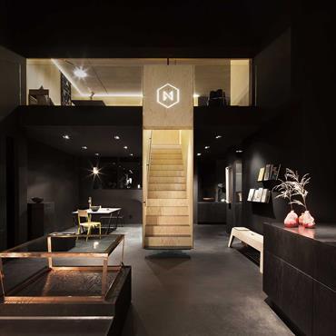 Pièce à vivre noire avec escalier central en bois menant à une mezzanine