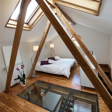 La chambre est accessible par un escalier. Le meuble sert de rangement et de garde corps. La charpente sépare la partie chambre de la partie sale de bain et encadre ...