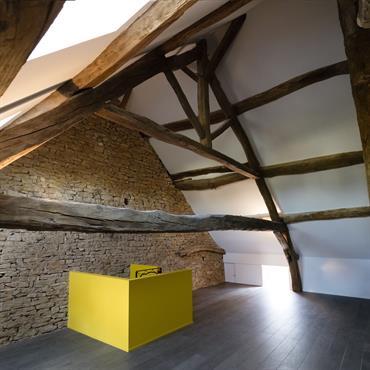 Aménagement des combles : côté authentique grâce aux poutres et au mur en pierre, ajout de modernité avec l'escalier jaune