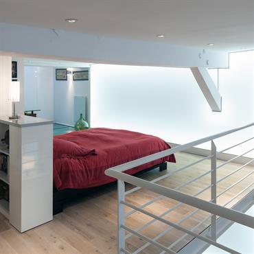 La tête de lit délimite l'espace de la chambre du loft, intègre un poteau structurel des rangements dissimulés sur les côtés et une bibliothèque.