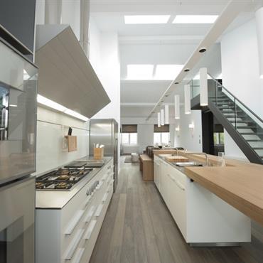 Grande cuisine en longueur, meubles blancs, plan de travail en bois. Double-hauteur