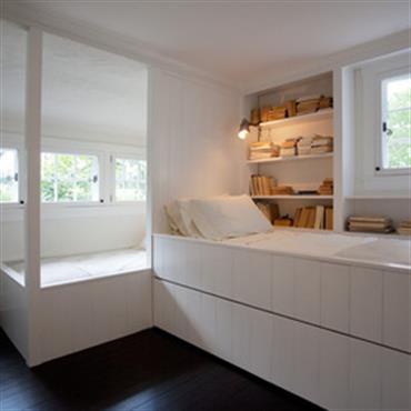 Chambre blanche et contemporaine pour deux enfants. Deux espaces sont créés grâce à la tête de lit, à la différence de niveaux et aux baies respectives