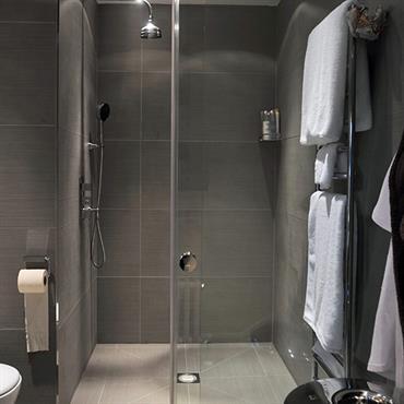 Dans cette douche à l'italienne, un carrelage gris a été choisi pour un rendu contemporain. Les deux nuances de gris donnent un caractère très déco à la salle de bain.