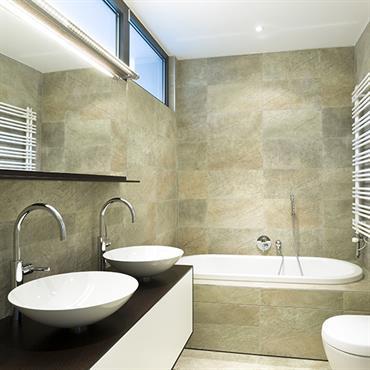 Salle de bain tendance chic avec carrelage aux murs, baignoire encastrée, WC et vasques posées sur un meuble suspendu.