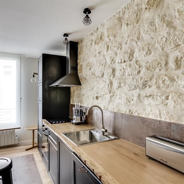 Cuisine avec mur en pierre claire qui donne toute l'originalité