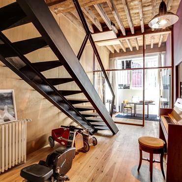 Mélange métal et bois avec cet escalier en acier et ces poutres apparentes en bois