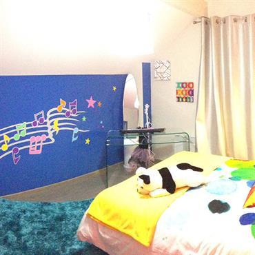 Chambre pour enfant avec partition de musique dessinée sur le mur. Murs de couleurs bleue et blanche