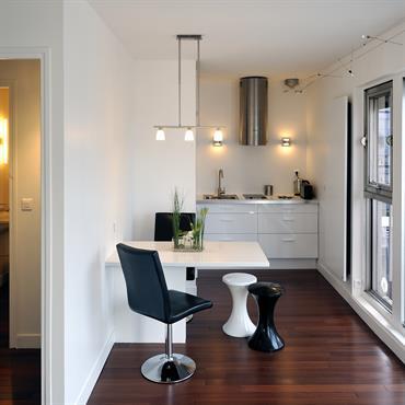 La cuisine vient se loger au bout d'une pièce de vie dans un petit renfoncement. Elle est à la fois mis un peu à l'écart du reste de la pièce ...