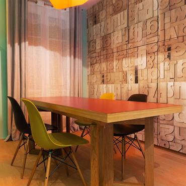 Salle à manger vintage avec un papier peint en relief effet lettres d'imprimeur en bois