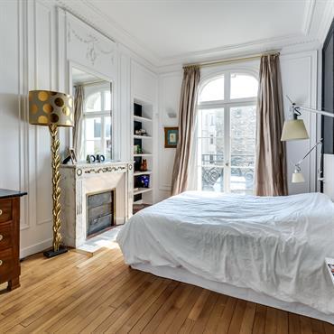 La suite parentale tout en longueur a été repensée: une tête de lit laquée blanc contraste avec la peinture bleu nuit Farrow and Ball.