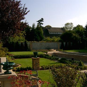 Jardin paysagé avec bassin central, allées, massifs de plantes et parties engazonnées