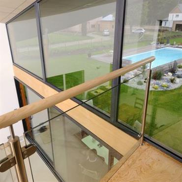 La mezzanine bénéficie de la lumière naturelle de la grande verrière protégée par l'avancée du toit en hélice.
