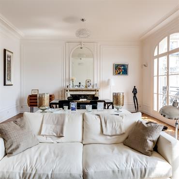 Grande pièce décloisonnée salon salle à manger. Les murs blancs et la sobriété du mobilier contribuent à éclaircir la pièce.