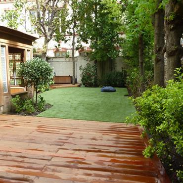 Petit jardin de ville avec terrasse en bois exotique ipé et gazon synthétique.