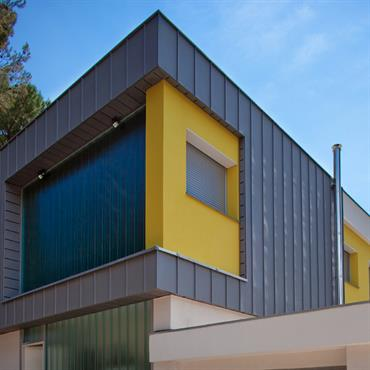 Villa avec façade en zinc, et mur béton jaune