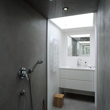 La salle de bain, mi blanche mi béton, offre la simplicité d'un environnement zen.