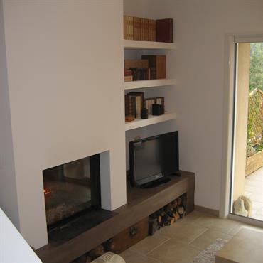 Bibliothèque et coin tv. La dalle de la cheminée est couverts de béton ciré d'un ton chocolat. La cheminée aux lignes épurées comporte un insert à guillotine.