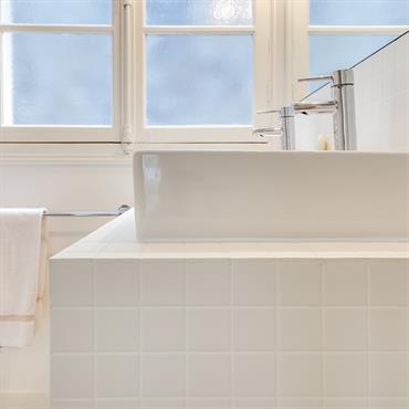 La vasque rectangulaire est posée sur un plan de travail habillé de carrelage en grès cérame blanc.