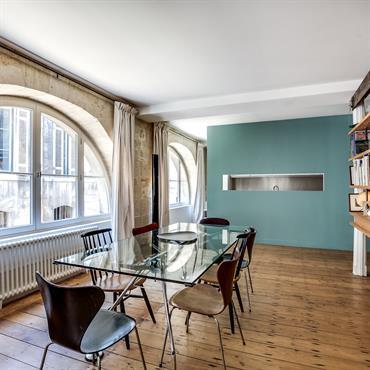 Fenêtre en demi-lune, mur vert canard et bibliothèque surélevée font l'originalité de la pièce