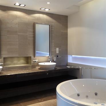 Double meuble vasque séparé par une niche centrale. Lumière artificielle orientée.