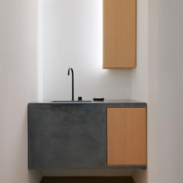 Salle de bain à l'épure maximale. Meuble vasque suspendu en béton ciré et placard en bois avec éclairage intégré.