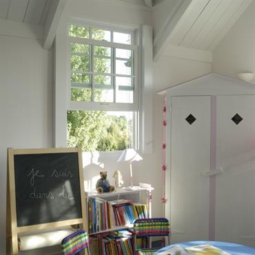 Chambre enfant avec poutres apparentes blanches. Table ronde en plastique bleu. Tableau ardoise et armoire pour enfant. Murs en bois blanc