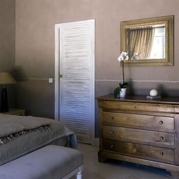 Chambre à l'esprit provençal dans des tons doux avec peinture décorative aux murs.